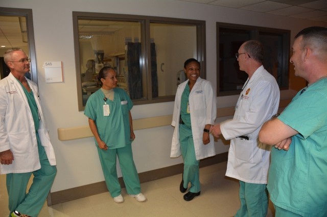 Brooke Army Medical Center Commander Col. Evan Renz talks with Air Force Capt. Shauna Butler, pediatrics resident, while Col. Douglas Soderdahl, Sgt. Maj. Rosalba Chambers and Command Sgt. Maj. Henry Chapman III look on during reverse cycle leadership rounding, Dec. 11, 2015.