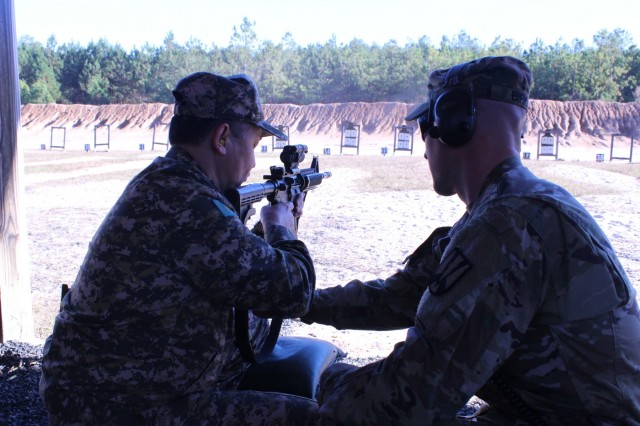 A drill instructor assists Gen. Maj. Mukhamedzhan Talasov recently on a Fort Jackson, S.C., range. Mukhamedzhan led a Kazakhstan contingent that visited to learn about all aspects of U.S. armed forces as Kazakhstan transitions from a conscript to an all-volunteer fighting force.