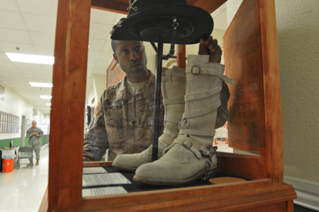Spc. Tamarkion Britton, a construction equipment repairer with 3d Cavalry Regiment, arranges the Cav Hat worn by Col. John Richardson, the 74th Colonel of the regiment, Jan. 5 inside 3d CR's headquarters building at Fort Hood, Texas. Britton built the display case for the items. (Photo by Staff Sgt. Tomora Clark 3d Cav. Regt. Public Affairs NCOIC)