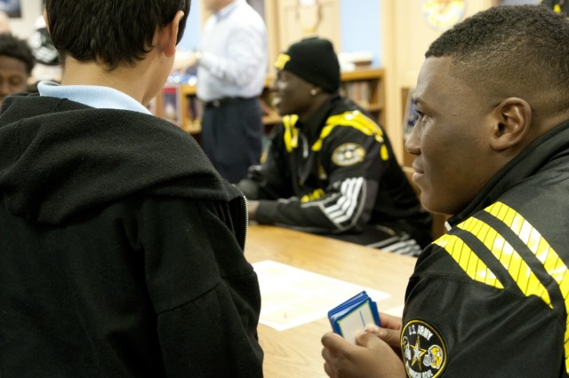 Derrick Brown, a Team East defensive lineman from Lanier High School in Buford, Ga., tries to stump a student on his multiplication skills at Boysville in San Antonio, Jan. 5, 2016.