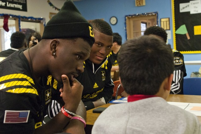 From right, Tavien Feaster, a Team East running back from Spartan High School in Spartanburg, S.C., and Derrick Brown, a Team East defensive lineman from Lanier High School in Buford, Ga., quiz a student at Boysville in San Antonio, Jan. 5, 2016, during a community outreach event for the Army All-American Bowl.
