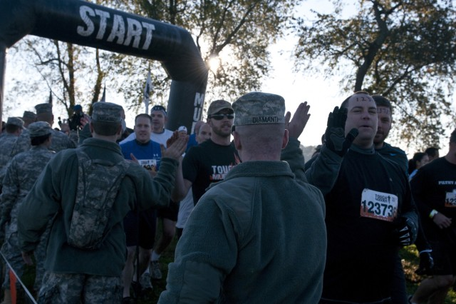 U.S. Army Reserve Pvt. Anthony Diamanti, 369th Engineer Detachment (Firefighting), a military and civilian firefighter from Berlington, N.J., offers encouragement to Tough Mudders during Tough Mudder Philly in Coatesville, Pa., Oct. 17. (U.S. Army photo by Staff Sgt. Debralee Best)