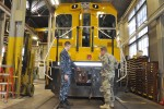 Army Lt. Col. David Callaway, right, Joint Munitions Command Reserve Detachment, inspects a railroad engine with Navy Lt. George Harlan, left, as they work on the Inter-Support Service Agreement that develops and executes a plan to functionally transfer rail operations and maintenance from the Navy Engineering and Facilities Command to Crane Army Ammunition Activity.