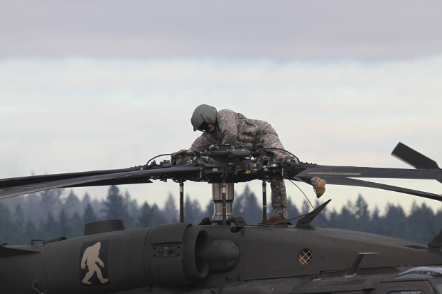 A U.S. Army Soldier assigned to 2-158th Assault Helicopter Battalion, 16th Combat Aviation Brigade, 7th Infantry Division prepares a UH-60 Black Hawk to depart from Joint Base Lewis-McChord, Washington for the National Training Center Jan. 9, 2016. The Soldiers and aircraft will participate in training with other units from 7th Infantry Division to prepare for future missions.