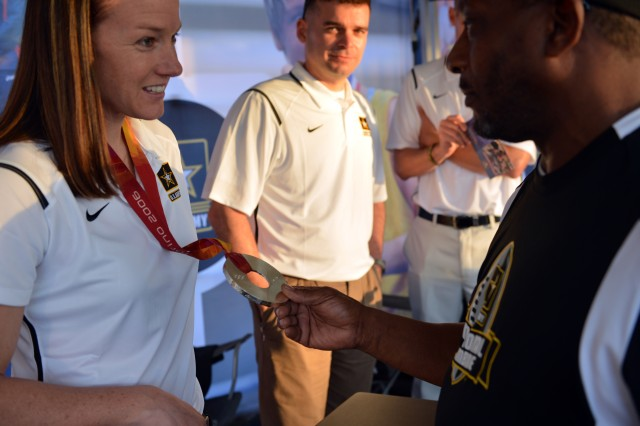 Retired Master Sgt. Renwick Jones, of Kansas City, Kansas, admires the Olympic silver medal of U.S. Army World Class Athlete Program bobsled coach Sgt. Shauna Rohbock, who won the medal as a competitor at the 2006 Olympic Winter Games.