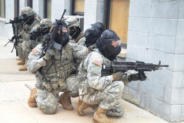 New York Army National Guard Soldiers, assigned to Company A, 1st Battalion 69th Infantry, check a street corner while training at the New York Police Department's urban training facility at Rodman's Neck in New York, Jan. 9, 2016.
