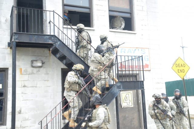 New York Army National Guard Soldiers, assigned to Company A, 1st Battalion 69th Infantry, head for the second floor of a building while training at the New York Police Department's urban training facility at Rodman's Neck in New York, Jan. 9, 2016.