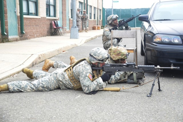 New York Army National Guard Soldiers, assigned to Company A, 1st Battalion 69th Infantry, cover enemy movement while training at the New York Police Department's urban training facility at Rodman's Neck in New York, Jan. 9, 2016.