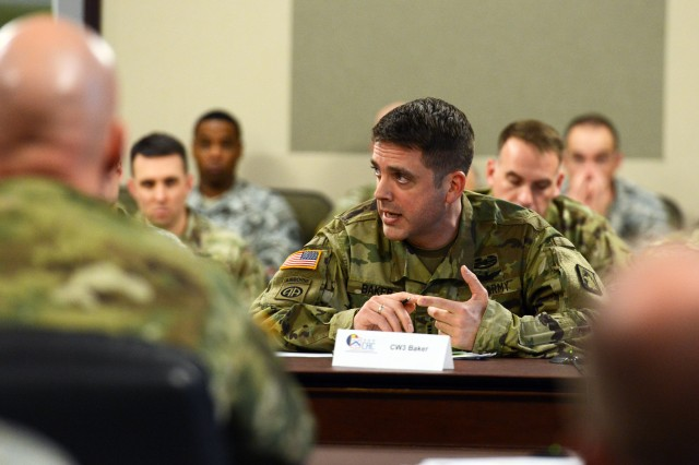 Chief Warrant Officer 3 James Baker presents his team's findings to  Lt. Gen. Robert Brown, commander of the Combined Arms Center, during the first-ever Warrant Officer Solarium, held at the Command and General Staff College, Fort Leavenworth, Kan., Jan. 15, 2016.