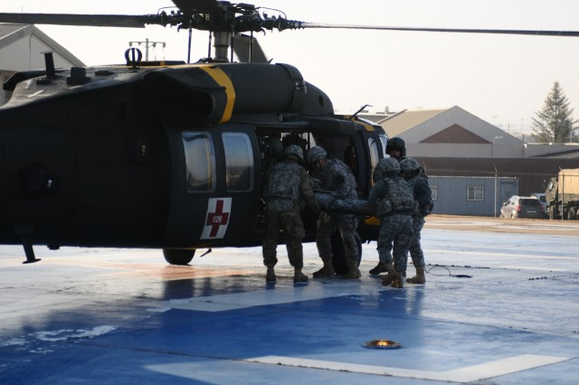 Medical specialists, of 210th Field Artillery Brigade, 2nd Infantry Division/ Republic of Korea-U.S Combined Division, load a patient into an active rotary aircraft during aeromedical evacuation training at the helipad of Troop Medical Clinic at Camp Casey, South Korea, Jan. 7, 2016.