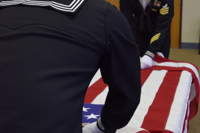 Sailors assigned to the Navy Center for Seabees and Facilities Engineering Detachment on Fort Leonard Wood practice folding the flag as part of their training for funeral details.