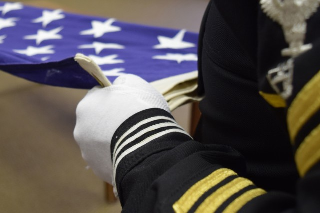 Navy Petty Officer 1st Class James Shipman, Heavy Equipment Operator Course instructor holds the flag during practice.