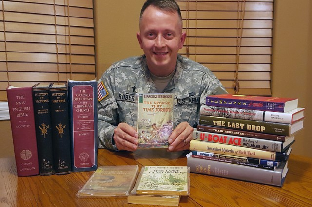 Chaplain (Maj.) Jeffrey Roberson, U.S. Army Engineer School ethics instructor, displays a few of his 900-book collection that includes a history book dating back to about 1836.