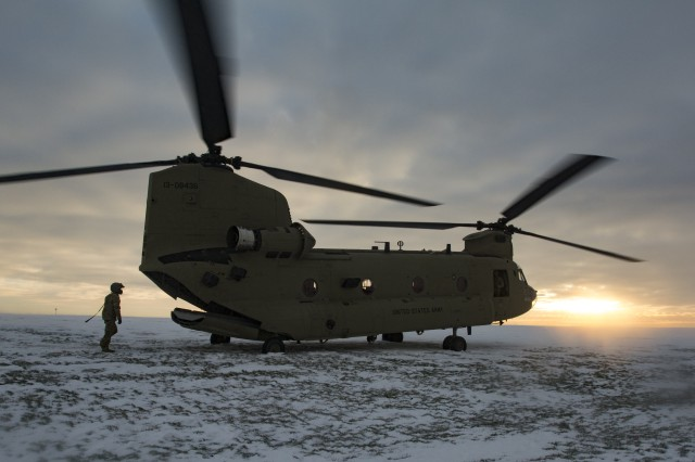 "Spc. Rader, Raymond a 15U CH-47 Helicopter Repairer, returns to his CH-47 Chinook after rigging and inspecting a payload prior to the sling load training. at Katterbach Army Airfield, Jan. 20, 2016. Aircrews practice flying in conditions of low visibility caused by ""whiteout"" in areas with loose snow.  Crews lower risk for future missions by conducting multiple training iterations in the snowy environment. (U.S. Army photo by Capt. Jaymon Bell, 12th CAB)"