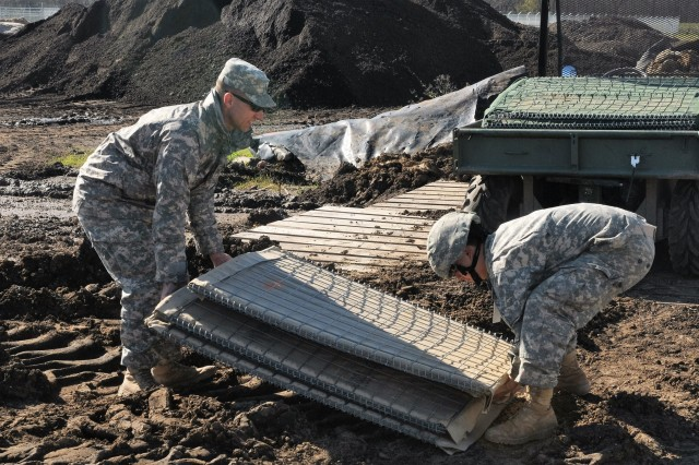 Soldiers lift wire-mesh barriers to build a levee to support Operation Winter River Flooding in Krotz Springs, La., Jan. 10, 2016.