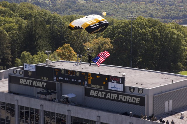 A member of the U.S. Military Academy at West Point Parachute team jumps in the Stars and Stripes before the Army v. Duke football game October 10, 2015 (U.S. Army photo by Thomas B. Hamilton III USAG West Point Public Affairs/released.)