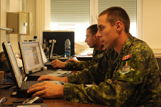 Cpl. Dave Bergeron and Pvt. Danny Gagne, members of the Canadian army, test the Multilateral Interoperability Program used to transmit information between nations during Combined Endeavor in Grafenwoehr, Germany, Sept. 19, 2016.