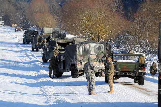 A convoy of U.S. Army vehicles moves to a simulated firing point over snow and ice at the U.S. Army's Joint Multinational Readiness Center in Hohenfels Training Area, Jan. 22, 2016.