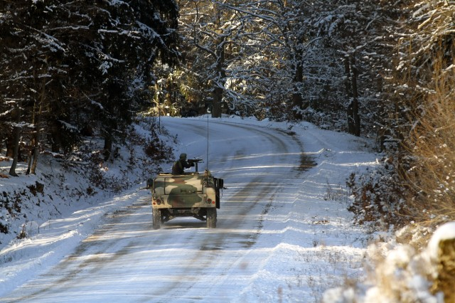 A U.S. Army gun truck, playing the role of a forward observer vehicle, treks through a snowed forest, Jan. 22, 2016, looking for an opposing force during react to contact training as part of Allied Spirit IV, a U.S. Army Europe exercise that unites seven nations for two weeks of tactical training at the Joint Multinational Readiness Center in Hohenfels Training Area, Germany.