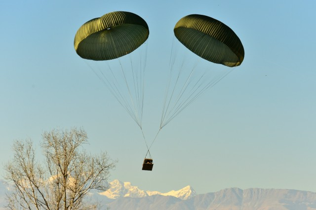 A Humvee belonging to the 173rd Airborne Brigade descends onto Frida IV Drop Zone, Jan. 21, 2016, after being dropped from a U.S. Air Force 86th Air Wing C-130 Hercules aircraft in Pordenone, Italy. The 173rd Airborne Brigade is the U.S. Army Contingency Response Force in Europe, capable of projecting ready forces anywhere in the U.S. European, Africa or Central Commands' areas of responsibility within 18 hours. (U.S. Army photo by Visual Information Specialist Paolo Bovo/Released)