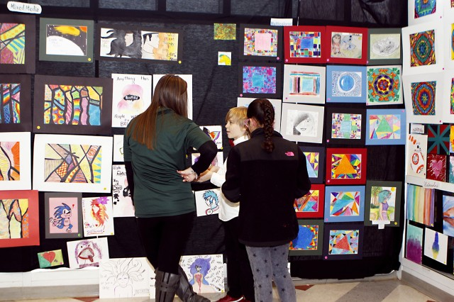A youth contestant at the 13th annual Fine Arts Festival hosted by The Boys and Girls Club of America and West Point Youth Services talks about the exhibition of artistic talent adorning the walls of the Middle School Teen Center, Jan. 8. There were more than 200 artists that entered (U.S. Army photo by Kathy Eastwood, USMA West Point, Public Affairs/released.)