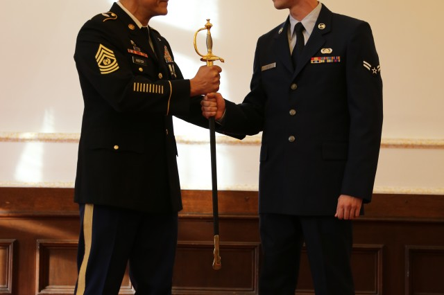 ANSBACH, Germany (Jan. 26, 2016) -- Retired Command Sgt. Maj. Mark A. Kiefer passes his Sword of the Noncommissioned Officer to his nephew Airman 1st Class Chase P. Kiefer following retired Command Sgt. Maj. Kiefer's relinquishment of command ceremony. U.S. Army Garrison Ansbach held a relinquishment of responsibility and retirement ceremony Jan. 8 at the Von Steuben Community Center here to farewell the now retired Command Sgt. Maj. Mark A. Kiefer. (U.S. Army photo by Bryan Gatchell, USAG Ansbach Public Affairs)
