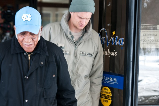 North Carolina National Guard Soldier Sgt. Colin Kalescky, assigned to the 105th Military Police Battalion Headquarters, Headquarters Company, helps escort Charles Harbison, an 86-year-old resident of Asheville, N.C., as he exits Davita Kidney Care Center following his dialysis treatment Jan. 23, 2016. Harbison called 911 emergency after discovering there was no way for him to make it to the center due to the severe winter weather and because of the overwhelming volume of emergency responses in the region, the NCNG was called to assist and transport Harbison in the hazardous conditions. (North Carolina National Guard photo by Sgt. Brian Godette, 382nd Public Affairs Detachment)
