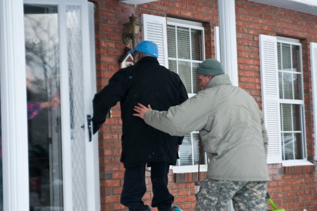 North Carolina National Guard Soldier, Sgt. Colin Kalescky, assigned to the 105th Military Police Battalion Headquarters, Headquarters Company, helps escort Charles Harbison, an 86-year-old resident of Asheville, N.C., as he returns home following his dialysis treatment Jan. 23, 2016. Harbison called 911 emergency after discovering there was no way for him to make it to the center due to the severe winter weather and because of the overwhelming volume of emergency responses in the region, the NCNG was called to assist and transport Harbison in the hazardous conditions. (North Carolina National Guard photo by Sgt. Brian Godette, 382nd Public Affairs Detachment)