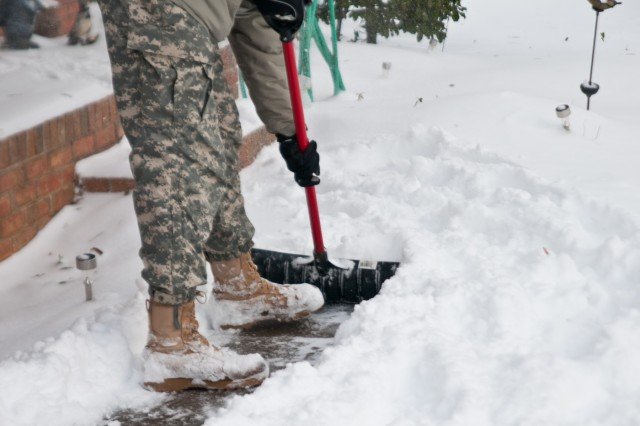 Following the safe return of Charles Harbison, an 86 year-old dialysis patient who was transported by a North Carolina National Guard winter storm catch team, Sgt. Colin Kalescky, assigned to the 105th Military Police Battalion Headquarters, Headquarters Company shoveled Harbison's walk way at his home in Asheville, N.C., Jan. 23, 2016. The North Carolina National Guard has been working with State Emergency Response partners for the last three days and have 100 Guardsmen mobilized in Eastern, Central and Western North Carolina to support local authorities. (North Carolina National Guard photo by Sgt. Brian Godette, 382nd Public Affairs Detachment)