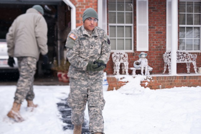 North Carolina National Guard Spc. Kevin Thomas, assigned to the 105th Military Police Battalion, Headquarters and Headquarters Company, salts the walkway for an elderly couple who have been stuck in their homes in the wake of Winter Storm Jonas in Asheville, N.C., Jan. 23, 2016. The North Carolina National Guard has been working with State Emergency Response partners for the last three days and have 100 Guardsmen mobilized in Eastern, Central and Western North Carolina to support local authorities. (North Carolina National Guard photo by Sgt. Brian Godette, 382nd Public Affairs Detachment)