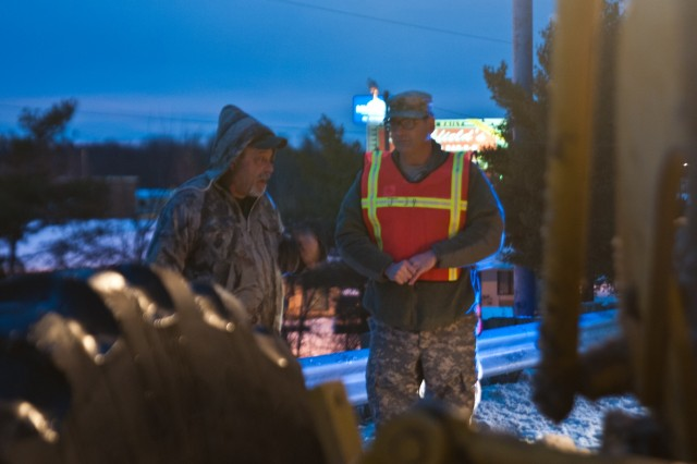 North Carolina National Guard Soldier, Staff Sgt. Brendan Stephens, assigned to the 382nd Public Affairs Detachment provides a wellness check on a Department of Transportation employee after seeing his snow plow had broken down on the side of a road in Greensboro, N.C., Jan. 24, 2016.The North Carolina National Guard has been working with State Emergency Response partners for the last three days and have 100 Guardsmen mobilized in Eastern, Central, and Western North Carolina to support local authorities. (North Carolina National Guard photo by Sgt. Brian Godette, 382nd Public Affairs Detachment)