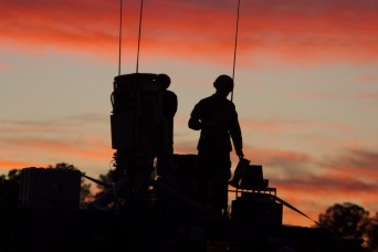 A Soldier of Company E, 3rd Combat Aviation Brigade installs radio communication equipment as the sun sets over Fort Stewart Jan. 25. (Photos by Spc. Scott Lindblom, 3rd CAB Public Affairs)