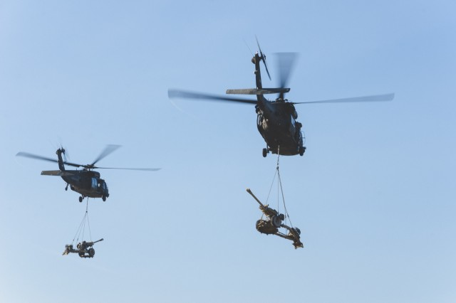 Blackhawk helicopters from 3rd Battalion, 227th Aviation Regiment, 1st Air Cavalry Brigade, 12th Combat Aviation Brigade, conduct M119A3 Howitzer Sling Load Operations, alongside 4th Battalion 319th Airborne Field Artillery Regiment, 173rd Airborne Brigade, during exercise Allied Spirit IV at the U.S. Army's Joint Multinational Readiness Center in Hohenfels Training Area, Germany, Jan. 26, 2016.An aviation task force made up of elements from 1st Battalion, 3rd Aviation Regiment, 12th Combat Aviation Brigade, Ansbach, and 3rd Battalion, 227th Aviation Regiment, 1st Air Cavalry Brigade, Fort Hood, Texas, provided attack, assault and medical evacuation support to exercise Allied Spirit IV from Jan. 10 - Feb. 5, 2016 at the U.S. Army's Joint Multinational Readiness Center, Hohenfels, Germany. (U.S. Army photo by Spc. Antonio Ramirez, 12th CAB)