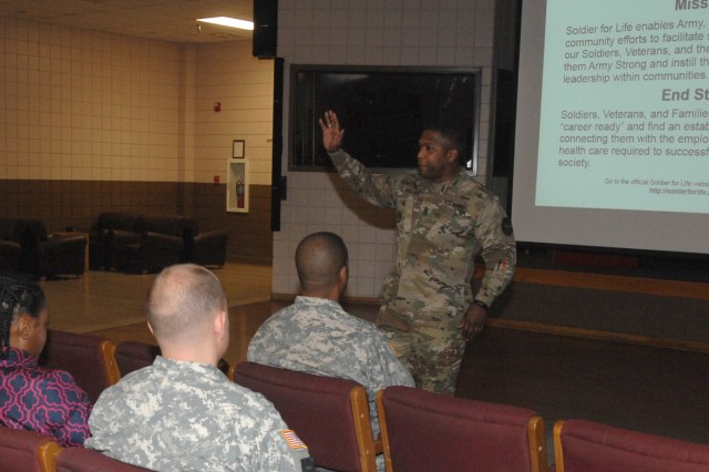 Command Sgt. Maj. Tyson Goolsby, U.S. Army Fort Leonard Wood Garrison, speaks to incoming Soldiers and spouses during the community orientation briefing held each Thursday at the Fort Leonard Wood USO as part of the Arrive Strong Program.