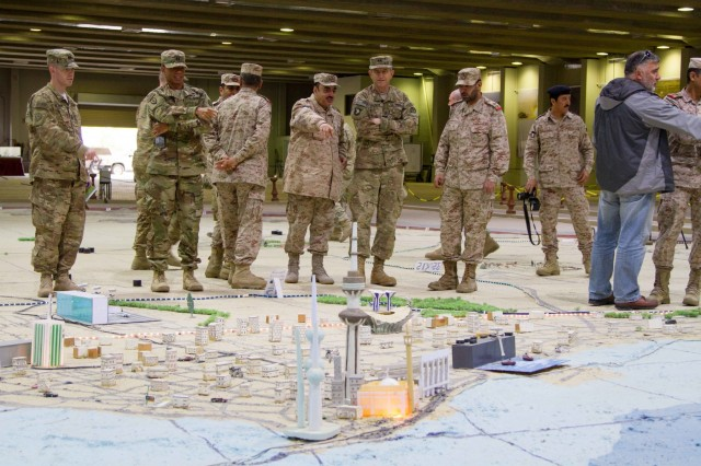 Maj. Gen. William Hickman, U.S. Army Central's deputy commanding general-operations, and USARCENT captains are oriented to the 35th Armored Brigade's sand table of Kuwait, a scale model of their country, during a leader development seminar at the Headquarters of the 35th Armored Brigade. The day's events focused on the role they played at the Battle of the Bridges, a large battle at the beginning of Saddam Hussein's invasion of Kuwait 25 years ago.