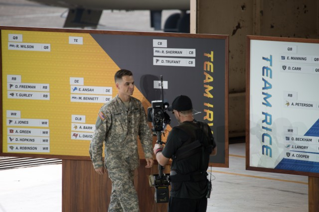 Spc. Jason Gamache, 25th Infantry Division Soldier of the Quarter, 2-25 Aviation Regiment, places the names of the Pro Bowl Draftees on the board during the live ESPN broadcast of the 2016 Pro Bowl Draft here, Jan. 27.
