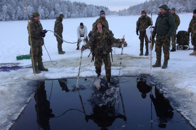 Capt. Kate Alfin, a Black Hawk Pilot with the 12th Combat Aviation Brigade, Ansbach Germany, plunges into the frigid water during the ice drill portion of the Allied Winter Course at the Norwegian School of Winter Warfare, Elverum, Norway, Jan. 15, 2016.  The Allied Winter Course provides students with basic knowledge and practical experience to operate in cold weather environment to include survival, mobility and leadership under winter conditions.