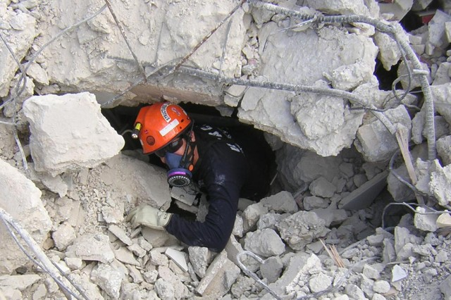 Scott Acone, P.E., a Structures Specialist from New England District, exits a void he has just searched at the collapsed 5-story Hotel Montana in Haiti following the 2010 earthquake.