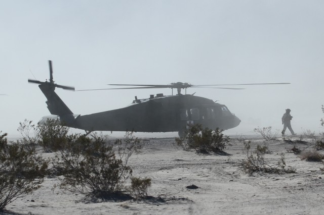 A U.S. Army Soldier assigned to 16th Combat Aviation Brigade walks through the dust of a UH-60 Black Hawk helicopter during decisive action rotation 16-03 at the National Training Center, Calif., Jan. 26, 2016. The Soldiers and aircraft from 16th CAB joined other units from 7th Infantry Division to prepare for future missions.