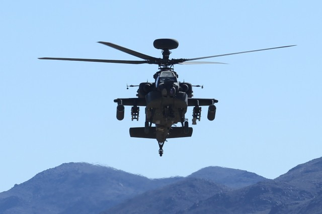 A U.S. Army AH-64E Apache helicopter assigned to 16th Combat Aviation Brigade flies overhead during decisive action rotation 16-03 at the National Training Center, Calif., Jan. 26, 2016. The Soldiers and aircraft from 16th CAB joined other units from 7th Infantry Division to prepare for future missions.