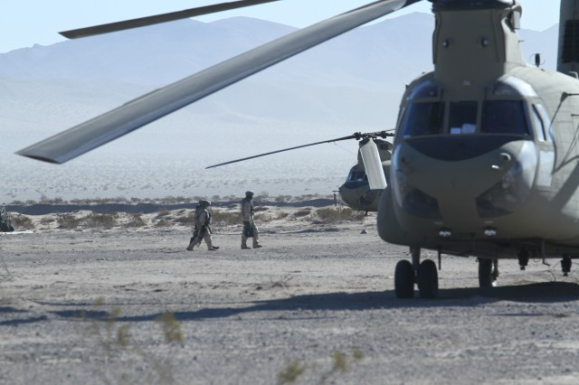 Two U.S. Army CH-47 Chinook helicopter crew chiefs assigned to 16th Combat Aviation Brigade prepare to board their aircraft during decisive action rotation 16-03 at the National Training Center, Calif., Jan. 26, 2016. The Soldiers and aircraft from 16th CAB joined other units from 7th Infantry Division to prepare for future missions.
