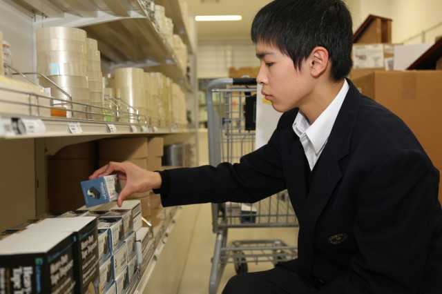 Hikaru Ito, 8th grader, from Shincho Junior High School organizes selling items on a shelf at Army Supply Center, the Logistics Readiness Center-Honshu, the 403rd Army Field Support Brigade during a job shadowing program from Jan. 14 to 15 on Camp Zama installation. (U.S. Army Photos by Noriko Kudo)