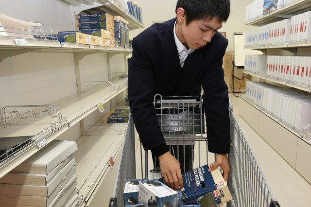 Hikaru Ito, 8th grader, from Shincho Junior High School places selling items on a shelf at Army Supply Center, the Logistics Readiness Center-Honshu, the 403rd Army Field Support Brigade during a job shadowing program from Jan. 14 to 15 on Camp Zama installation. (U.S. Army Photos by Noriko Kudo)