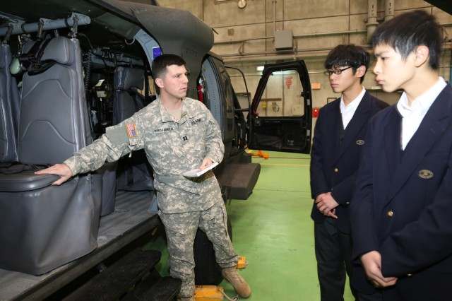 Cpt. Rafael A. Garcia-Menocal, commander of Headquarters and Headquarters Company, US Army Aviation Battalion Japan gives Hikaru Ito and Leo Toyooka, 8th graders, from Shincho Junior High School a tour in the Hanger during a job shadowing program from Jan. 14 to 15 on Camp Zama installation. (U.S. Army Photos by Noriko Kudo)