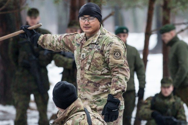 Sgt. 1st Class Augustin Evangelista, a platoon sergeant with L Troop, 3rd Squadron, 2nd Cavalry Regiment, explains battle drill movements to a Soldier during team leader training in Rukla, Lithuania, Jan. 26, 2016.