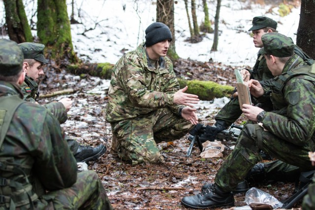 Soldiers, from the Lithuanian Duke Vaidotas Mechanized Infantry Battalion, listen as they receive comments during an after-action report from Sgt. Richard Bowen, an infantryman and squad leader with L Troop, 3rd Squadron, 2nd Cavalry Regiment in Rukla, Lithuania, Jan. 28, 2016.
