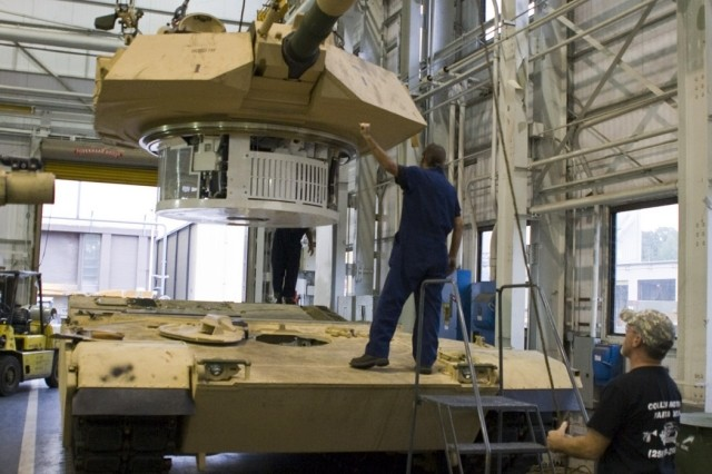 ANAD employees guide a repaired turret to an M1A2 hull.