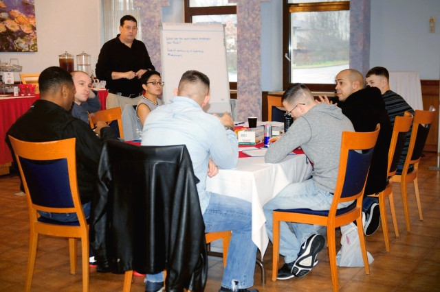 "Kaiserslautern, Germany -- Jeffrey E. Fite, Ph,D, U.S. Army Research Institute  (standing, left) listens as soldiers discuss how to build healthy relationships within their squads at the ""Not in my Squad"" focus group at Armstrongs Club, Jan. 28. The campaign was initiated by Sgt. Maj. of the Army Daniel A. Daily and is meant to help empower squad leaders in developing a positive climate within their ranks. (Photo by Staff Sgt. Betty Y. Boomer, 21st TSC Public Affairs)"
