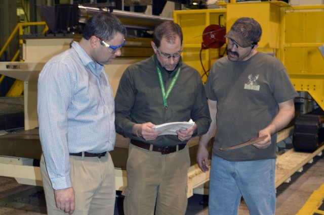 "From left, Business Transformation Chief Scott Shadle, Manufacturing Supervisor Dale King, and Machinist Clint Brock look over a ""Traveler"" for the 155mm howitzer tube that is behind them.  One of the goal's of LMP II is to digitize the Traveler, which documents every machining operation for each product."