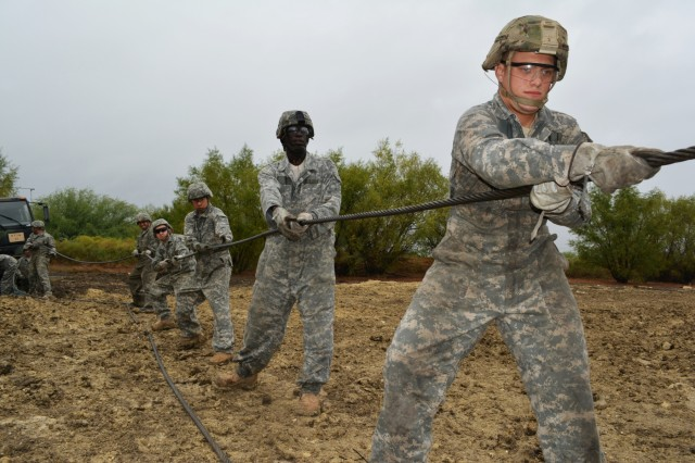 Photo credit: Students attending the Wheeled Vehicle Recovery Course at Regional Training Site Maintenance-Fort Hood, Texas, unravel a winch cable from a tow truck to connect the cable to a truck wedged in mud, Oct. 23, 2015. The course teaches Army mechanics how to properly and safely recover and tow vehicles that may be stuck or inoperable. (U.S. Army photo Sgt. 1st Class Phillip Eugene)